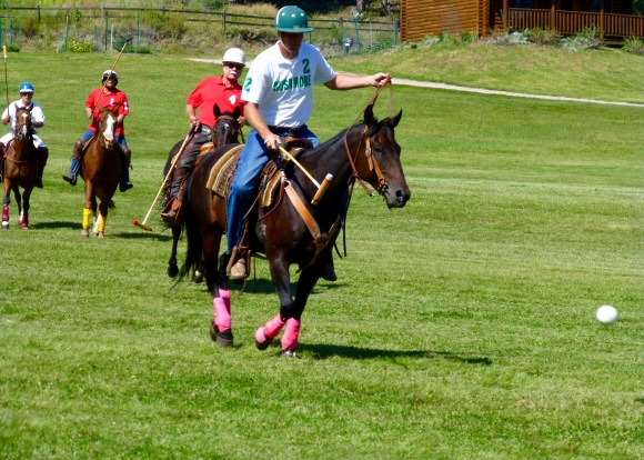 Rushmore Polo & Social Club's Dan Gylten (white #2) moves the ball down field while being closely followed by opposing Black Hills Polo Club's Rich Jensen (red #4) and Kurt Ketelsen (red #1). Fellow team member Tim Gregson (white #1) brings up the rear.
