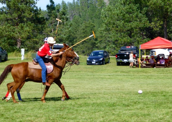 Duane Lammers (red #3) playing for Rapid City's Black Hills Polo Club is neck-in-neck with Hill City's Rushmore Polo & Social Club's Boe Gregson (white #3) in pursuit of the ball.
