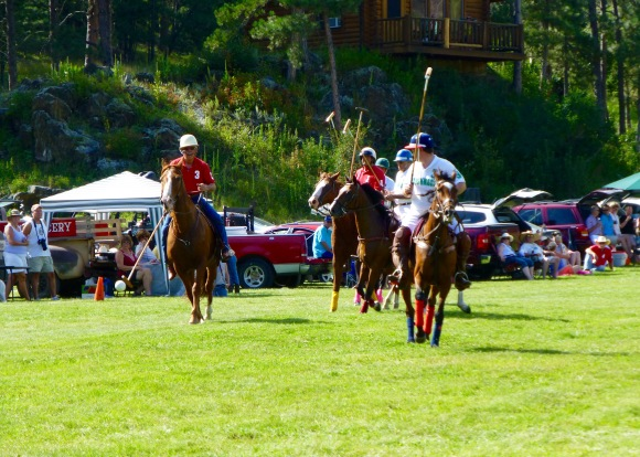 Rapid City's Duane Lammers breaks away with possession of the ball as fellow teammate Kurt Ketelsen (red #1) and the entire Hill City Rushmore Polo & Social Club pursues.